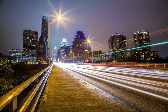 Light trails in a long exposure taken taken of the night time skyline of Austin, Texas as the lights of passing cars stretch into the distance.