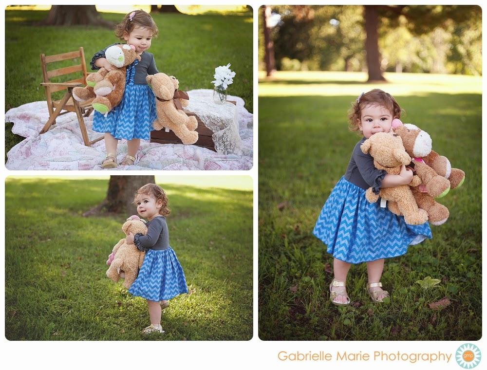 Little girl in blue chevron dress carries around her stuffed animals in the park.