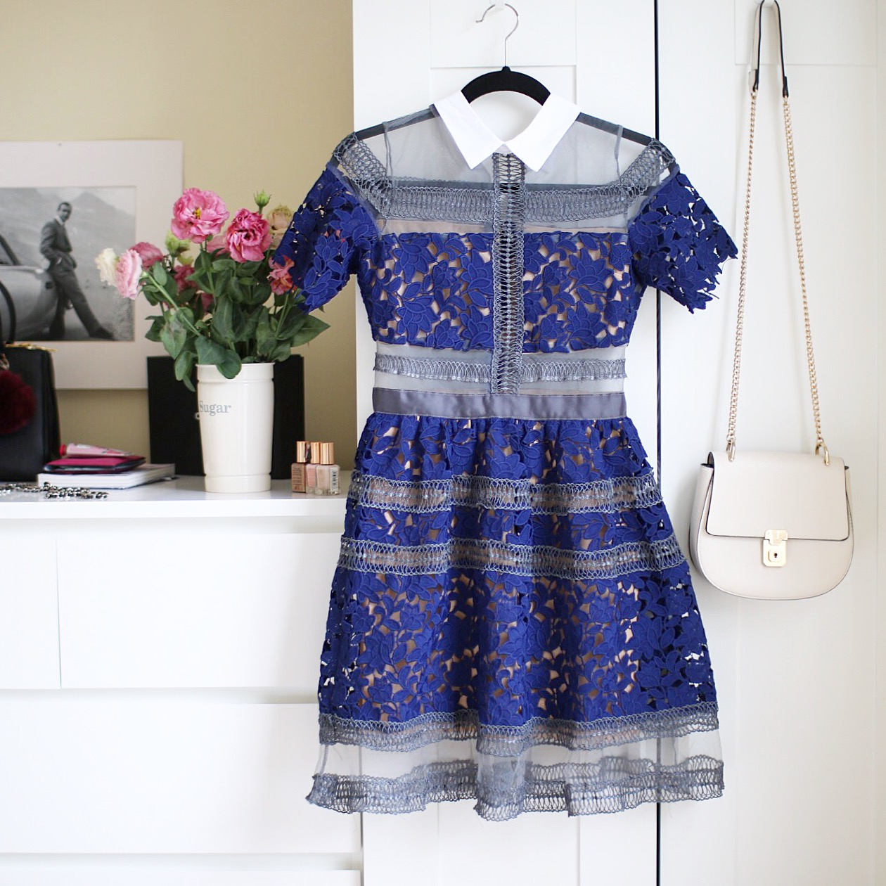 a feminine blue lace dress with sheer panels hangs in front of a closet door with an chloe drew bag