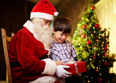 Santa Claus y un niño junto al arbol de Navidad