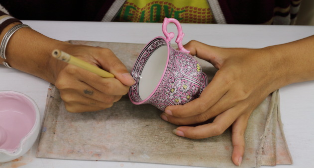 Intricate Benjarong Painting being made on a tea cup at Benjarong village, Thailand