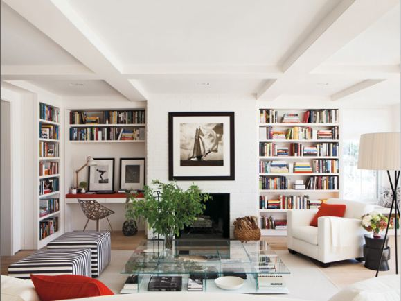 elle decor's nantucket retreat with a white living room, built in book shelves, striped ottomans and glass coffeetable
