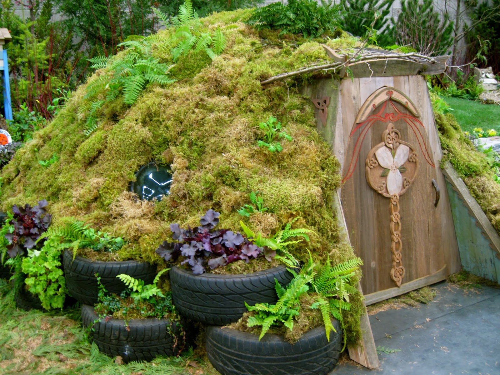 A Cute Hobbit House, Covered In Moss And Ferns And Poppies, But The Tires  Seem Out Of Place, Like They Wandered In From A Different Garden.