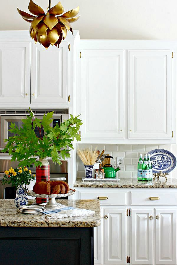 white kitchen cabinets, black island, brass hardware, lotus pendant light
