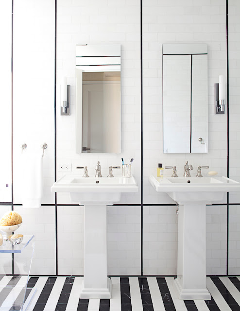 russell groves's black and white bathroom with black and white striped tile floor, two pedestal sinks and long mirror with white paneled wall with black dividers