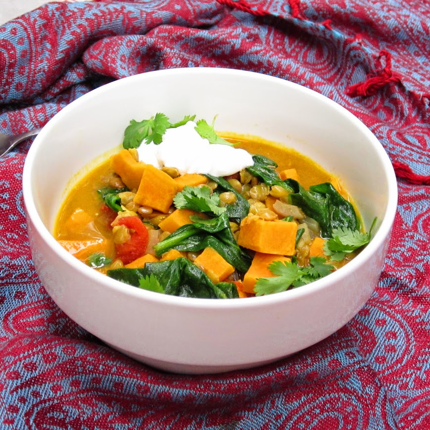 Bowl of sweet potato and spinach daal on a traditional fabric