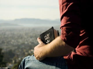 Man on hill holding Bible