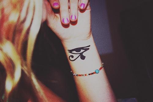 Chica Rubia con un tatuaje del ojo de horus en la muñeca