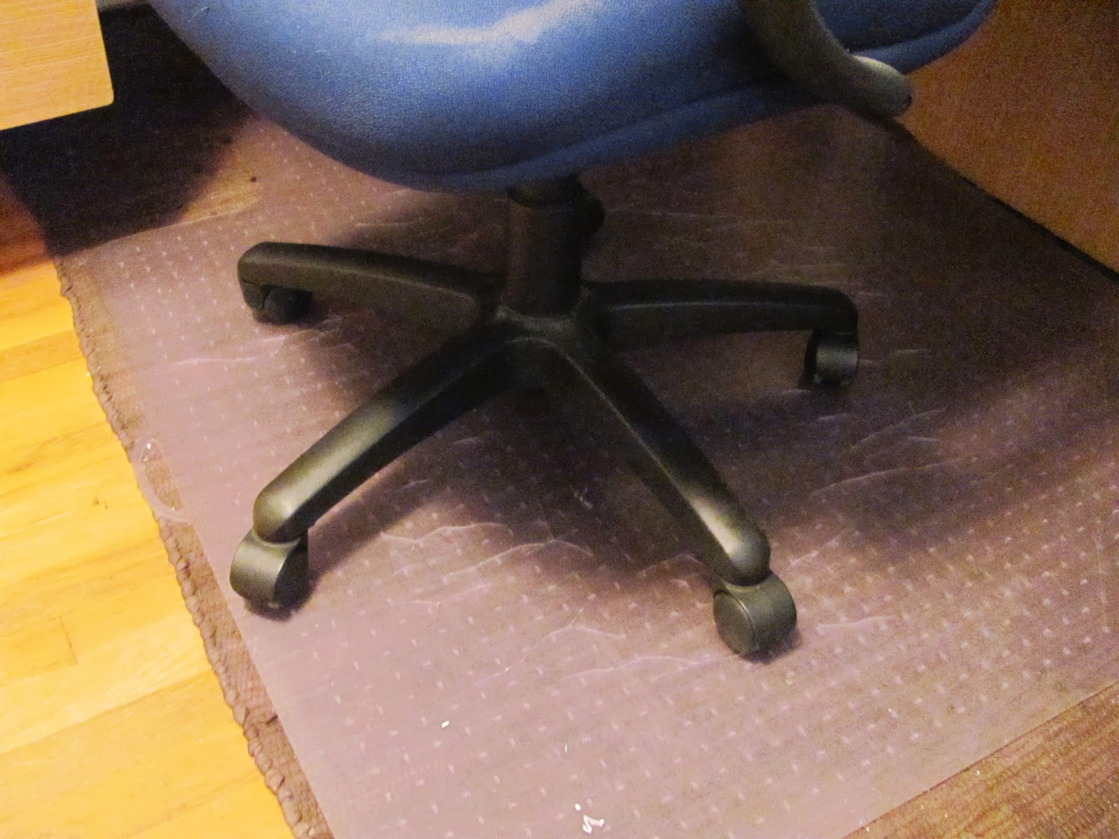 The plastic floor cover has some cracks as the wheels of the computer chair rest upon it