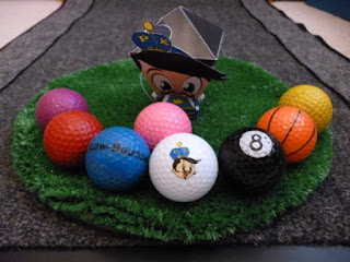 #PKSH2 - The Putter King wobblehead next to 8 different coloured golf balls