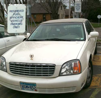 White Cadillac beater parked in a spot marked Reserved fuel-efficent vehicle parking only