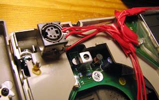 [Image: Another part of the insides of the radio, with the addition of a hotglued Mini-DIN socket.]