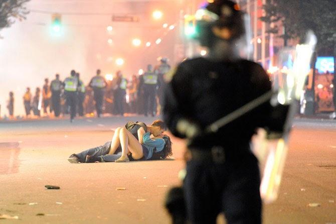 Парень помогает своей девушке встать во время демонстрации, вспыхнувшей после проигрыша хоккейной команды в Ванкувере, Канада, 2011 год.