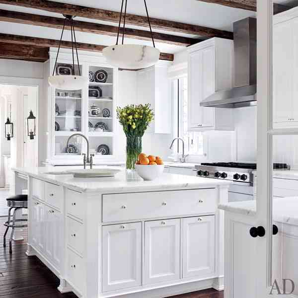 white kitchen with stainless appliances and restained wood flooring