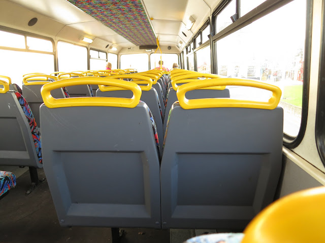 Grey seats with yellow handles on the top of a double-decker bus