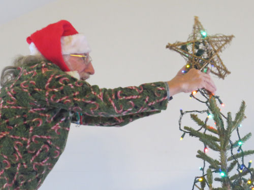putting star on Christmas Tree