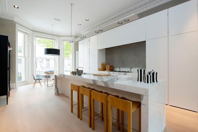 cocina en blanco y marmol moderna con silla eames y barra americana