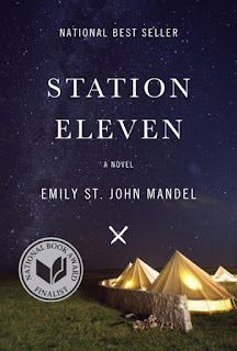 Book cover, 'Station Eleven,' a novel by Emily St. John Mandel. Cover art depicts a night-time scene of tents behind a barrier wall. An emblazon on the cover identifies the novel as a National Book Award Finalist.
