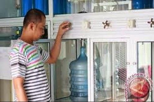 seorang pegawai depo air minum isi ulang sedang mengisi galon