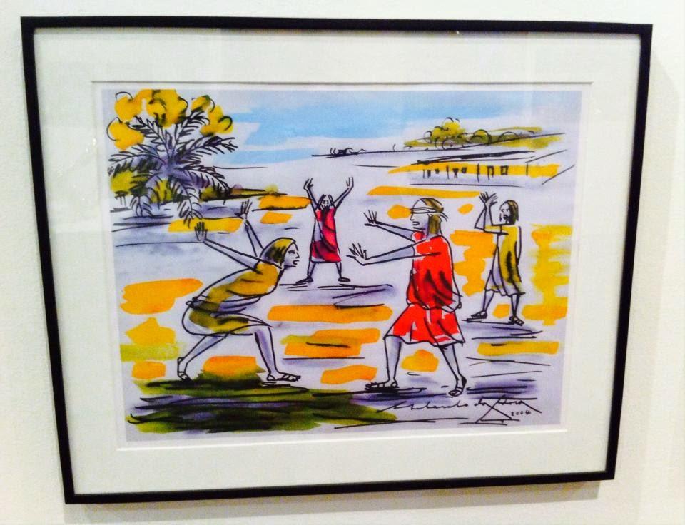 Descrição da foto: Gravura com quatro meninas usando vestido, duas em vermelho e duas em amarelo. Elas brincam de cabra-cega. Uma delas está com uma venda nos olhos enquanto as outras estão em volta gesticulando os braços. Estão em um terreno colorido de amarelo e verde. No fundo uma folhagem e uma casa.