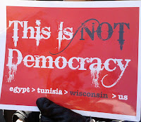sign saying, This is not democracy.  Egypt then Tunisia then Wisconsin then US