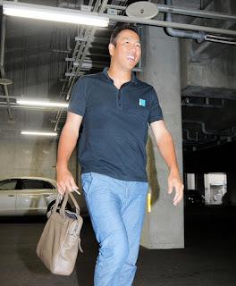 患部の右手で荷物を持ち、笑顔で球場に姿を見せた広島・黒田博樹=マツダスタジアム(撮影・出月俊成)