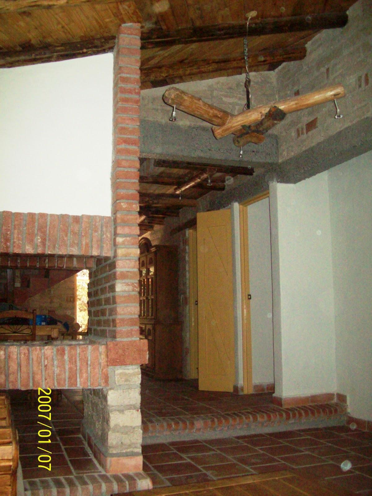 vista de la sala hacia el comedor y atraves de la chimenea de dos bocas con los diseos genuinos en candiles de madera rustica cabaa ubicada en paseo de