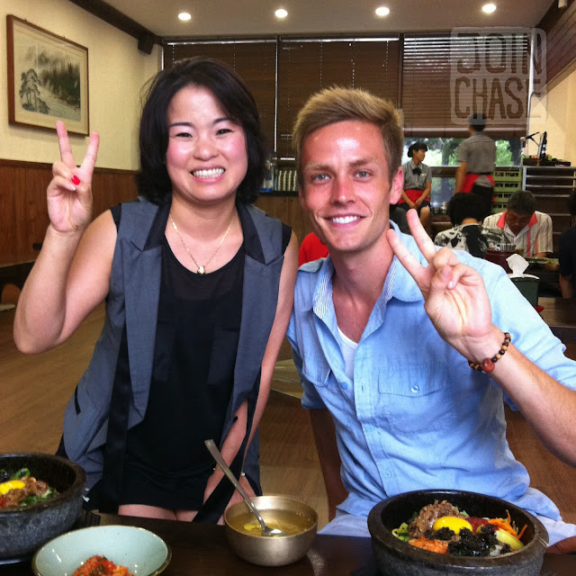 A Korean woman and foreigner pose for a photo with bibimbap in Jeonju, South Korea.