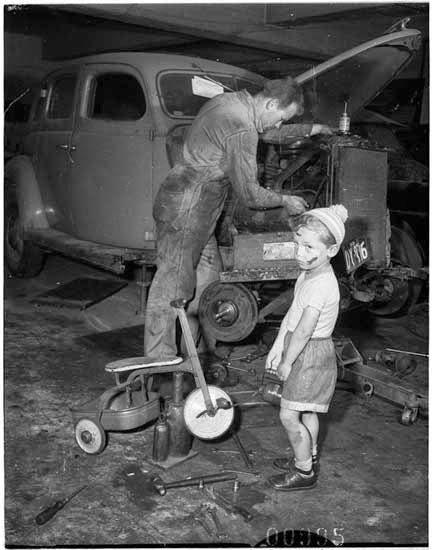 Young-boy-with-dinky-in-car-workshop-while-his-father-services-a-car-Bondi-6-October-1955