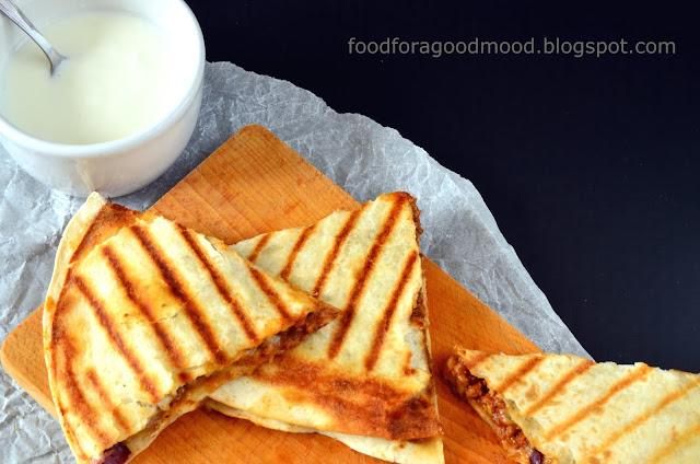 Ale Meksyk!  Dziś na obiad quesadillas, czyli coś w rodzaju meksykańskiej pizzy. Dwa placki tortilli, a między nimi farsz z mielonej wołowiny, pomidorów i czerwonej fasoli. Do tego ser - duuużo sera, który pod wpływem ciepła cudownie rozpuszcza się i ciągnie w nieskończoność ;) A gdy dodamy do tego jeszcze bukiet aromatycznych przypraw... Poezja smaku! Koniecznie spróbujcie i dajcie znać, czy quesadillas podbiły Wasze serca :)