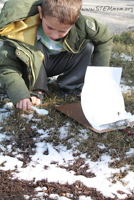 Boy collecting snow sample to test pH as a STEM lab: STEMmom.org