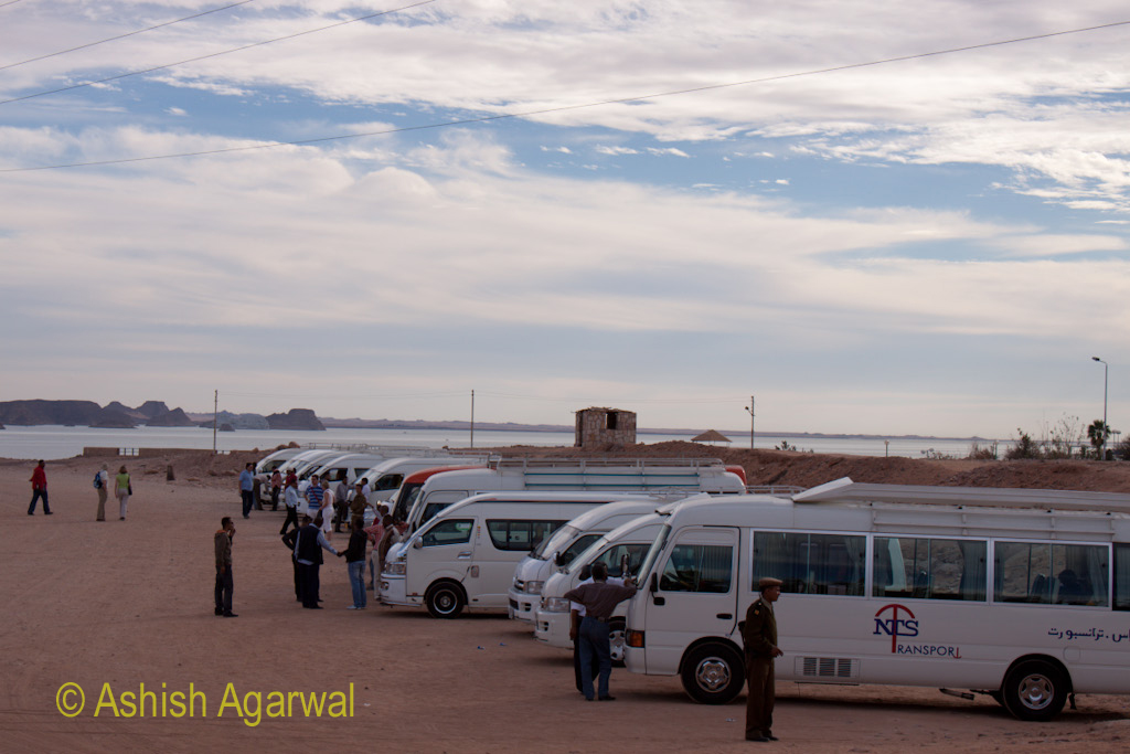 People in front of tourist buses under a cloudy sky at the temple of Abu Simbel in Egypt