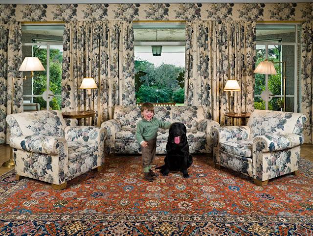 Cuadro de Ouka Leele de un salón muy recargado con el estampados de flores de los sofás, cortinas y alfombra. Hay un niño sonriendo acariciando a un perro con la lengua fuera.