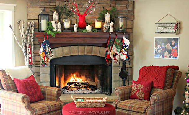 Stone fireplace with plaid Basset chairs and ottoman and birch logs with candles-www.goldenboysandme.com