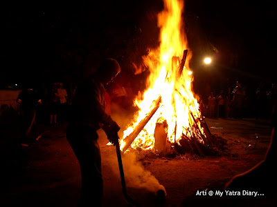 Taking of coconut prasad from the Holika Dahan bonfire