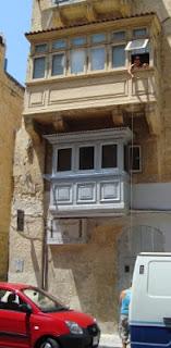 Mujer bajando una cesta por el balcón en Malta