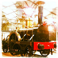 A very old steam engine, red and black with a shiny metal funnel.