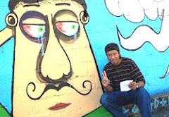 Valter Luis ao lado de um Cartoon na parede