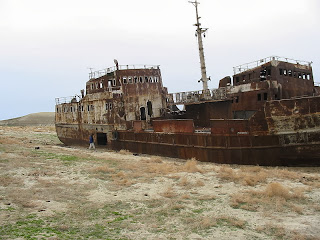 The hulk of a ship, resting upon the dry and barren remains of the Aral Sea.