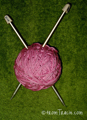 Ball Of Pink Yarn And Knitting Needles