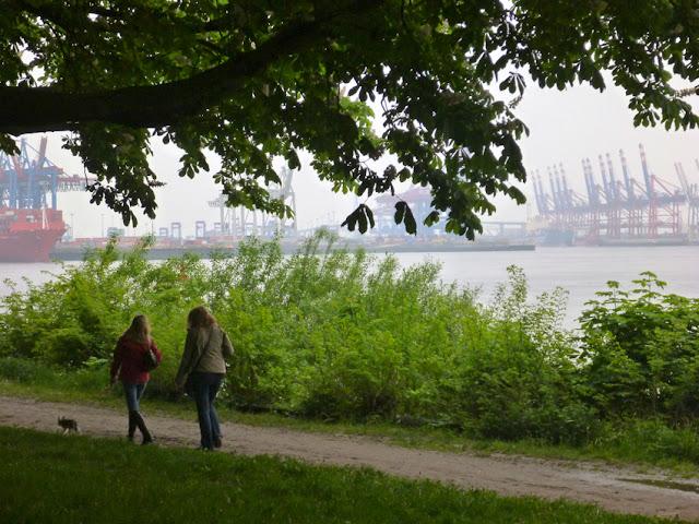 Blick auf Spaziergängerinnen im Grünen, im Hintergrund scheint der Hamburger Hafen durch