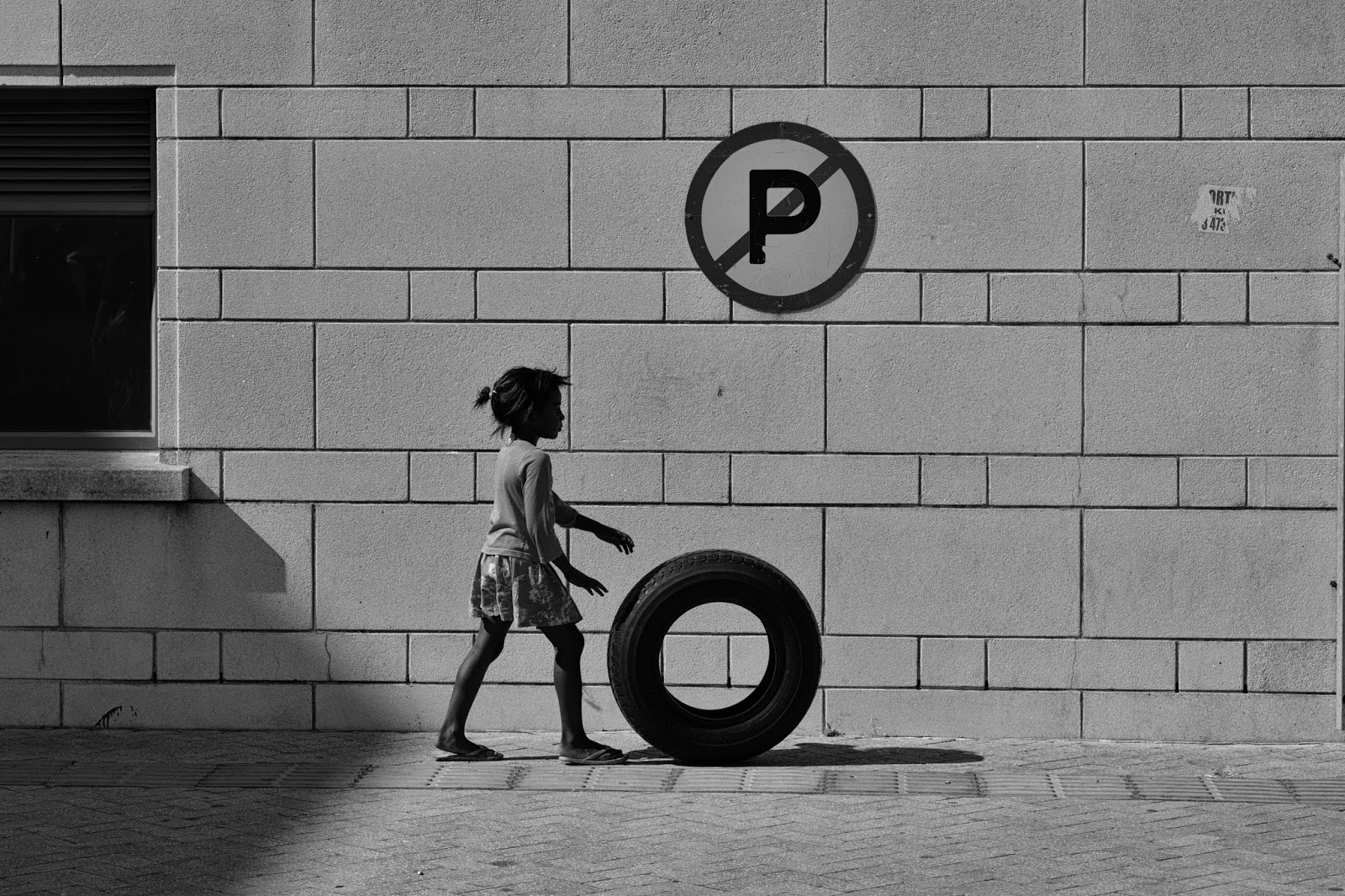 A girl pushes a tyre past a no parking sign in this South African street photograph