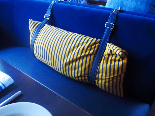 close up of yellow striped pillows attached with  buckles