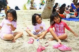 anak kecil bermain pasir di pantai