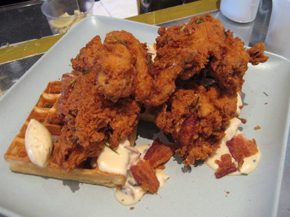 Fried chicken with mushroom sausage gravy, bacon and waffles. Enough ...