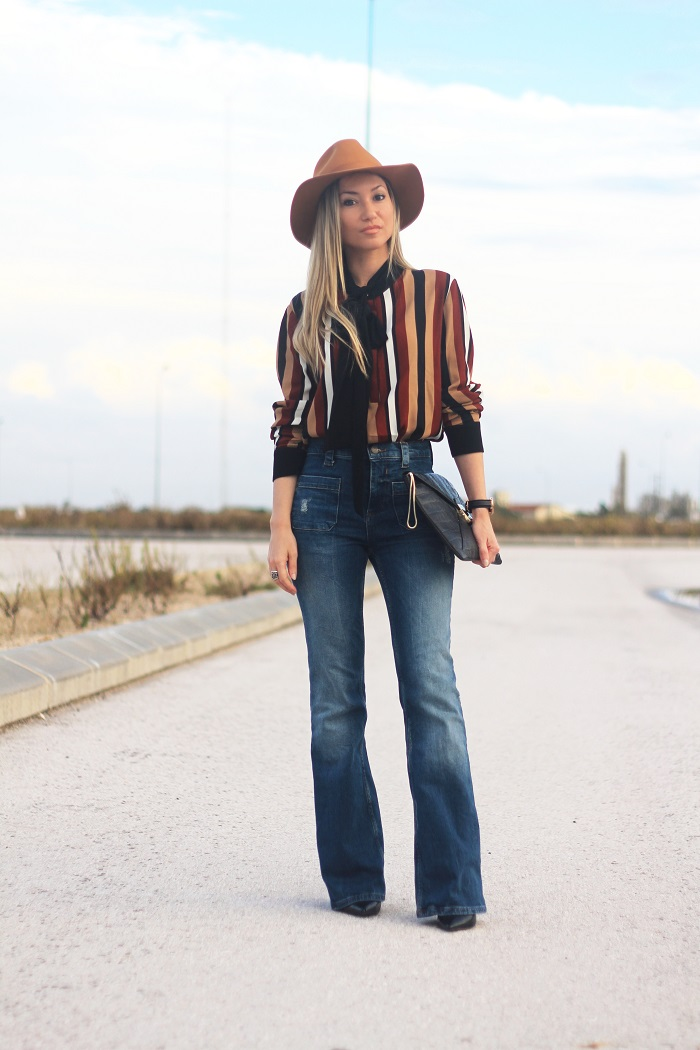 Os Anos 70 estão aí em força e o Look do dia de hoje representa esta tendência. As flare jeans (calças à boca-de-sino) alongam as pernas e toda a silhueta. Outfit. Dicas de Moda e Imagem. Daniel Wellington. Riscas. Blusa de laçada. Tendências Outono/Inverno 2015-2016. Style Statement. Blog de moda portugal.