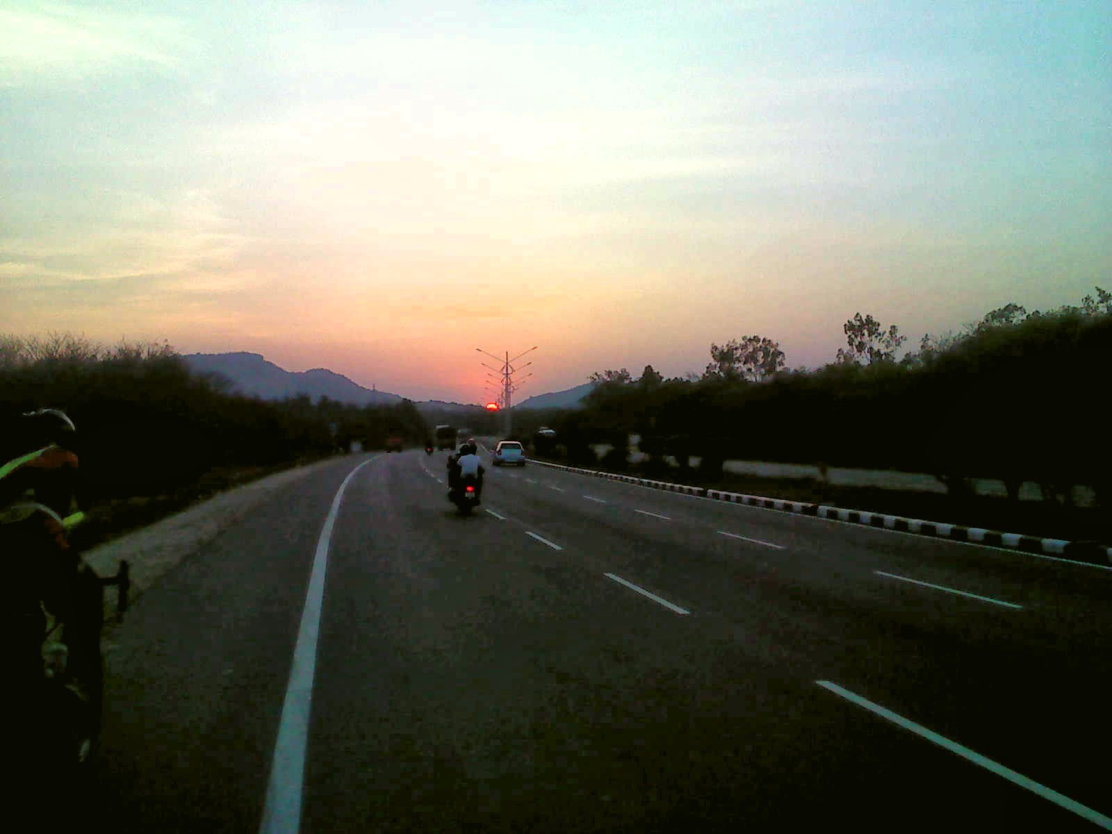 Randonneur cycling into the Sunset on Chennai highway near Bargur and Krishnagiri