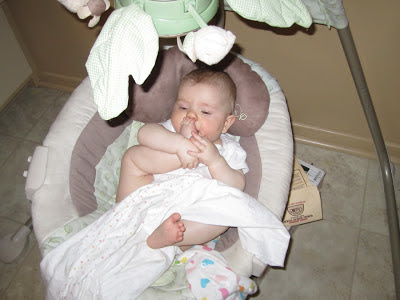 baby chewing on toes in swing