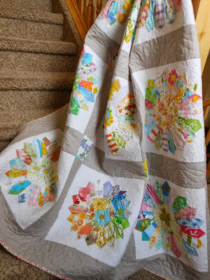 a dresden quilt draped over a banister made using floral vintage sheetss