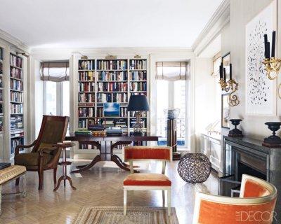 decorar la pared con candelabros dorados de velas antiguas. butacas antiguas de color naranja. estanterias de pladur en salon